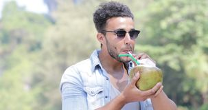 Το ισπανικό άτομο πίνει το κοκτέιλ καρύδων πέρα από τους φοίνικες, ευτυχής χαμογελώντας νέος λατινικός τουρίστας τύπων απόθεμα βίντεο
