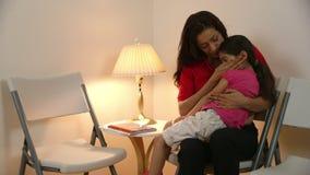 Το ισπανικό mom περιμένει στη αίθουσα αναμονής κλινικών το γιατρό να δουν οι άρρωστοι απόθεμα βίντεο