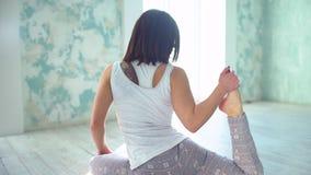 Το ισχίο τεντώματος γυναικών χαλιών γιόγκας, μπλοκάρει τους μυς, οι μυ'ες ποδιών με το περιστέρι θέτουν το τέντωμα η δεκαετία του φιλμ μικρού μήκους
