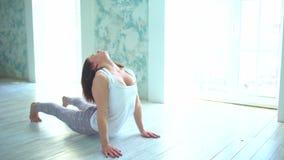 Το ισχίο τεντώματος γυναικών χαλιών γιόγκας, μπλοκάρει τους μυς, οι μυ'ες ποδιών με το περιστέρι θέτουν το τέντωμα η δεκαετία του απόθεμα βίντεο
