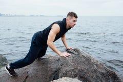 Το ισχυρό άτομο ενεργεί γιόγκα στην παραλία βράχων το πρωί ενάντια στη θάλασσα Στοκ Εικόνες