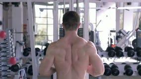 Το ισχυρό άτομο bodybuilder εκτελεί μια άσκηση για την κατάρτιση οικοδόμησης μυών στον προσομοιωτή έλξης για τα όπλα εργαζόμενο απόθεμα βίντεο