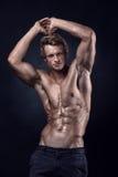 Το ισχυρό αθλητικό άτομο παρουσιάζει το σώμα και κοιλιακούς μυς στοκ φωτογραφία