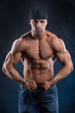 Το ισχυρό bodybuilder τεντώνει τους ισχυρούς μυς του στοκ εικόνες