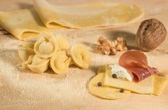 Το ιταλικό σπιτικό tortellini, ανοικτός και κλειστός, γέμισε με το τυρί και το prosciutto ricotta, το μαύρα πιπέρι και τα ξύλα κα Στοκ Εικόνες