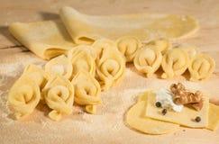 Το ιταλικό σπιτικό tortellini, ανοικτός και κλειστός, γέμισε με το τυρί ricotta, τα ξύλα καρυδιάς και μερικά σιτάρια του μαύρου π Στοκ φωτογραφία με δικαίωμα ελεύθερης χρήσης
