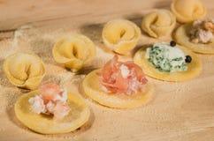 Το ιταλικό σπιτικό tortellini, ανοικτός και κλειστός, γέμισε με το τυρί ricotta, τις γαρίδες, το prosciutto, το φρέσκα σπανάκι κα Στοκ Φωτογραφία