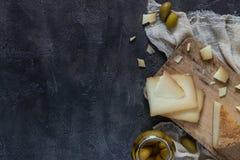 Το ιταλικό toscano pecorino σκληρών τυριών τεμάχισε και τεμάχισε στον ξύλινο πίνακα με τις πράσινες ελιές Στοκ εικόνα με δικαίωμα ελεύθερης χρήσης