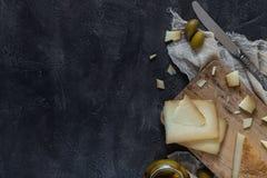 Το ιταλικό toscano pecorino σκληρών τυριών τεμάχισε και τεμάχισε στον ξύλινο πίνακα με το μαχαίρι και τις πράσινες ελιές, διάστημ Στοκ φωτογραφία με δικαίωμα ελεύθερης χρήσης