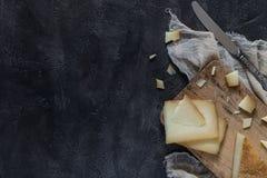Το ιταλικό toscano pecorino σκληρών τυριών τεμάχισε και τεμάχισε στον ξύλινο πίνακα με το μαχαίρι, διάστημα αντιγράφων Στοκ Φωτογραφία