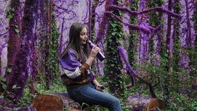 Το ιώδες παραμύθι που το δασικό κορίτσι σε ένα αθλητικό σακάκι κάθεται στο κολόβωμα στο α το πορφυρό δάσος και ξεβιδώνει το καπάκ απόθεμα βίντεο