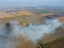 Το κάψιμο του αχύρου ρυζιού στους τομείς Καπνός από το κάψιμο του αχύρου ρυζιού στους ελέγχους Πυρκαγιά στον τομέα Στοκ Εικόνες