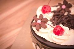 Το κέικ γενεθλίων, κεράσι σοκολάτας βανίλιας ήταν διαιρεμένα κομμάτια σε έναν ξύλινο πίνακα Στοκ Εικόνα
