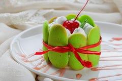 Το κέικ με την κρέμα και τα κεράσια σε ένα καλάθι της πράσινης ζύμης, έδεσαν το α Στοκ φωτογραφίες με δικαίωμα ελεύθερης χρήσης