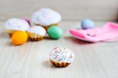 Το κέικ Πάσχας και τα ζωηρόχρωμα αυγά σε έναν άσπρο πίνακα Στοκ Φωτογραφίες