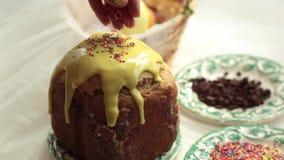 Το κέικ Πάσχας με το κίτρινο πάγωμα και ζωηρόχρωμος ψεκάζει σε έναν άσπρο πίνακα Το γλυκό σιτάρι κοριτσιών ψεκάζει το κέικ Πάσχας απόθεμα βίντεο