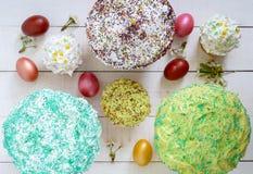 Το κέικ Πάσχας kulich με το λούστρο, ζωηρόχρωμη ζάχαρη ψεκάζει Χρωματισμένα χρωματισμένα αυγά Στοκ Εικόνες