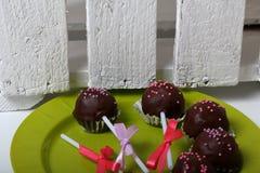 Το κέικ σκάει διακοσμημένος με ένα τόξο της πλεξούδας Σε ένα πιάτο Δίπλα στο ξύλινο κιβώτιο, χρωματισμένο λευκό στοκ φωτογραφίες με δικαίωμα ελεύθερης χρήσης