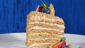 Το κέικ στρώματος με η φράουλα και τα βακκίνια στο πιάτο Κέικ θερινών μούρων Κομμάτι του πολυστρωματικών μούρου και του φυστικιού φιλμ μικρού μήκους