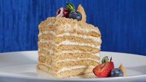 Το κέικ στρώματος με η φράουλα και τα βακκίνια στο πιάτο Κέικ θερινών μούρων Κομμάτι του πολυστρωματικών μούρου και του φυστικιού απόθεμα βίντεο