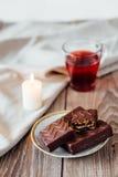 Το κέικ Browny έτοιμο να φάνε στο άσπρο πιάτο με το φλυτζάνι καφέ και το περιοδικό κρατούν την επιτραπέζια κορυφή Στοκ Φωτογραφίες
