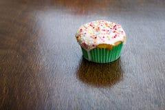 Το κέικ Cupcake ένα μεταχειρίζεται άθικτο ψεκάζει το ξύλινο υπόβαθρο Στοκ Φωτογραφίες