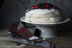 Το κέικ Pavlova με η κρέμα και τα μούρα Στοκ Εικόνες