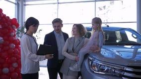 Το κέντρο πωλήσεων αυτοκινήτων, καταναλωτικό ζεύγος με το παιδί συμβουλεύει με το αυτόματο κατάστημα εργαζομένων για την αγορά το απόθεμα βίντεο