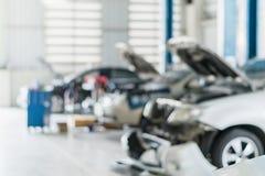 Το κέντρο υπηρεσιών επισκευής αυτοκινήτων που θολώνεται μας χρησιμοποιεί αυτοκινητικό υπόβαθρο επισκευής τεχνικών συντήρησης στοκ φωτογραφία