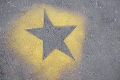 το κίτρινο αστέρι είναι χρωματισμένο στην γκρίζα άσφαλτο στοκ εικόνα με δικαίωμα ελεύθερης χρήσης