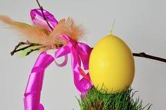 Το κίτρινο αυγό Πάσχας στη χλοώδη στρογγυλή επιφάνεια, διακοσμητική κτυπά korbash στο υπόβαθρο Στοκ εικόνα με δικαίωμα ελεύθερης χρήσης
