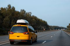 Το κίτρινο αυτοκίνητο με τους μεταφορείς φορτίου στεγών οδηγεί κατά μήκος του καλοκαιριού στοκ φωτογραφίες με δικαίωμα ελεύθερης χρήσης