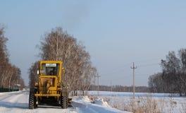 Το κίτρινο γκρέιντερ τρακτέρ αφαιρεί το χιόνι από το δρόμο καθαρίζει το ταξίδι το χειμώνα στοκ εικόνα με δικαίωμα ελεύθερης χρήσης