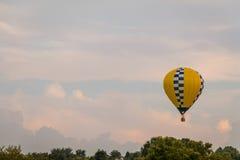Το κίτρινο και μπλε διαμορφωμένο μπαλόνι ζεστού αέρα επιπλέει μεταξύ των βουνών σε έναν όμορφο ουρανό α στην έκθεση της Farmer `  Στοκ φωτογραφία με δικαίωμα ελεύθερης χρήσης