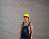 Το κίτρινο κράνος εμπορευμάτων γυναικών τεχνικών με την γκρίζα ποδιά τζιν μπλουζών και τζιν ντύνει τη στάση και παραδίδει την τσέ στοκ εικόνα με δικαίωμα ελεύθερης χρήσης