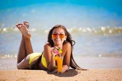 Το κίτρινο μαγιό γυναικών Brunette πίνει το κοκτέιλ Στοκ Φωτογραφία
