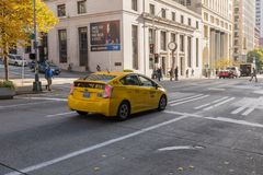 Το κίτρινο ταξί σταμάτησε σε έναν φωτεινό σηματοδότη στη στο κέντρο τη στοκ φωτογραφία