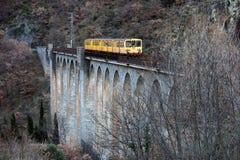 Το κίτρινο τραίνο Jaune τραίνων στη γέφυρα Sejourne Στοκ Φωτογραφία