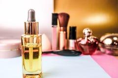 Το κίτρινο χρυσό διαφανές βάζο γυαλιού με το πετρέλαιο εγχυτήρων, makeup βασίζει στο υπόβαθρο ενός πίνακα makeup για την ομορφιά στοκ εικόνες