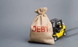 Το κίτρινο forklift φορτηγό δεν μπορεί να ανυψώσει την τσάντα με το χρέος επιγραφής Ανικανότητα να ξεπληρωθεί ένα δάνειο, αναδόμη στοκ φωτογραφίες