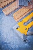 Το κίτρινο stapler μέταλλο πυροβόλων όπλων συρράπτει τις ξύλινες σανίδες στο μεταλλικό backgro Στοκ Εικόνα