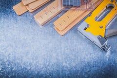 Το κίτρινο stapler χρώμιο πυροβόλων όπλων συρράπτει τις ξύλινες σανίδες στη μεταλλική πλάτη Στοκ εικόνα με δικαίωμα ελεύθερης χρήσης