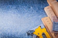Το κίτρινο stapler tacker μέταλλο πυροβόλων όπλων συρράπτει τις ξύλινες σανίδες σε μεταλλικό Στοκ Φωτογραφία