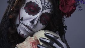 Το καθαρισμένο κορίτσι makeup μιας νεκρής νύφης σε αποκριές, αγκαλιάζει ένα ανθρώπινο κρανίο απόθεμα βίντεο