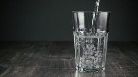 Το καθαρό νερό χύνει αργά στο γυαλί φιλμ μικρού μήκους
