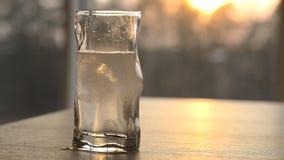 Το καθαρό νερό χύνεται σε ένα γυαλί στο ηλιοβασίλεμα απόθεμα βίντεο