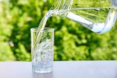 Το καθαρό πόσιμο νερό χύνεται από μια κανάτα σε ένα γυαλί Στοκ Εικόνες