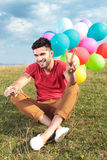 Το καθισμένο περιστασιακό άτομο με τα μπαλόνια παρουσιάζει νίκη Στοκ εικόνα με δικαίωμα ελεύθερης χρήσης