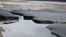 Το κακό κοίλωμα ασφάλτου είναι μεγάλος δρόμος βροχής λακκούβας υπαίθριος απόθεμα βίντεο
