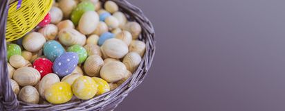 Το καλάθι με τα ξύλινα κομμάτια προς κατεργασία των αυγών Πάσχας, αυγά που χρωματίζονται στα διαφορετικά χρώματα, απομονώνει το κ στοκ εικόνα
